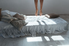 Slim legs of young woman flying in air above bed Royalty Free Stock Images