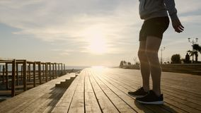 Sportsman is squatting in sunny evening on city embankment, detail view of body. Slim male athlete is training his legs, doing squats, view on body. Work out of stock footage