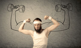 Slim male wants to be strong. A young college student with beard and glasses posing in front of grey background, thinking about lifting weight with big muscles Royalty Free Stock Photos
