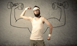 Slim male wants to be strong. A young college student with beard and glasses posing in front of grey background, thinking about lifting weight with big muscles Stock Images