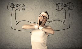 Slim male wants to be strong. A young college student with beard and glasses posing in front of grey background, thinking about lifting weight with big muscles Royalty Free Stock Photography