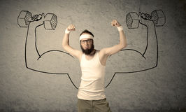 Slim male wants to be strong. A young college student with beard and glasses posing in front of grey background, thinking about lifting weight with big muscles Stock Photo