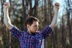 Slim man hipster in plaid shirt shows his muscles in forest. Self-irony. Slim man hipster in plaid shirt shows his muscles in forest. Self-irony concept Stock Images
