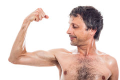 Slim man looking at biceps Royalty Free Stock Images