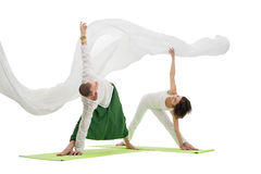 Slim man and woman doing yoga exercises in studio Royalty Free Stock Photos