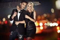 Slim paar die met de paraplu lopen stock afbeelding