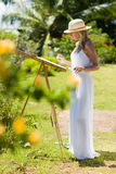 Slim painter woman in white dress and hat in tropical environment Stock Images