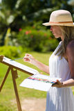Slim painter woman in white dress and hat in tropical environment Royalty Free Stock Images