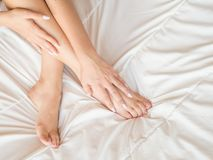 Slim, perfect and beautiful crossed woman legs on bed. Cropped image of erotically lying on bed beautiful woman in. Bedroom. Crumpled white bedclothes royalty free stock photography