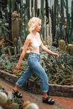 Slim perky female model walking confidently among succulents Royalty Free Stock Photo