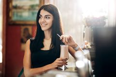 Slim pretty girl is standing next to bar in the fitness club and keeping a glass with cocktail in her hand stock image
