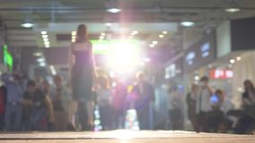 Slim professional model in black dress on high heels defiles the podium in backlight during a fashion show