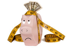 Slim Savings. This poor piggy bank is getting slimmer and slimmer.  Many people have had to use their savings to pay bills, etc.  A skinny piggy bank with tape Stock Photo