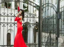 A slim, sensual brunette in a long red dress is standing by the wrought iron gates. Fashion photo. Royalty Free Stock Images