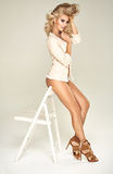 Slim, sensual lady leaning on the white chair Stock Images