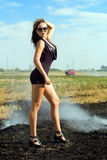 Slim brunette. Posing in the smoky field royalty free stock images