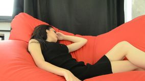 Slim brunette in black dress lays on a red couch stock footage