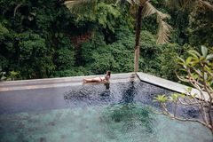 Slim brunette woman in swimsuit relaxing on edge tropical infinity pool in jungle. Palms around and crystal clean royalty free stock image