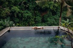Slim brunette woman in swimsuit relaxing on edge tropical infinity pool in jungle. Palms around and crystal clean water. royalty free stock photos