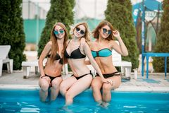 Slim sexy women in swimsuits sitting by poolside Stock Photo