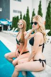 Slim sexy women in swimsuits sitting by poolside Royalty Free Stock Image