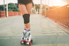 Slim and sexy young women and roller skates. Summer active vacations in the city. Extreme sports Stock Photo