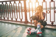Slim and sexy young women and roller skates. Summer active vacations in the city. Extreme sports. Stock Photography