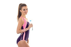 Slim sheerful sports girl in magenta body swimsuit with bottle of water and measure tape smiling on camera isolated on Royalty Free Stock Photography