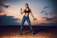 Slim sports woman. Young sexy slim sports woman training on field and sky background at twilight. Tattoo on body Royalty Free Stock Photo