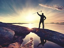 Slim sportsman on nord sea coast. Hiker open arms to the sunrise stand at seaside  boulder. Slim sportsman on nord sea coast. Hiker open arms to greeting the sun Stock Images
