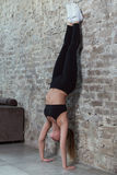 Slim sportswoman doing wall hand stand practicing yoga in a flat with loft interior royalty free stock image