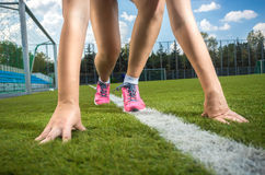 Slim sporty woman getting ready to run on grass track Royalty Free Stock Photo