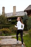 Slim sporty woman running upstairs . Beautiful girl on training trail in leggings and sneakers. Wooden houses on Stock Images