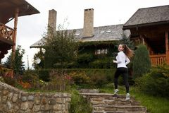 Slim sporty woman running upstairs . Beautiful girl on training trail in leggings and sneakers. Wooden houses on Stock Photo