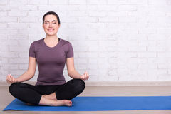 Slim sporty woman sitting in yoga pose on mat over white brick w Stock Images