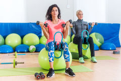 Slim sporty women training sitting on exercise balls holding dumbbells and squeezing Pilates Ring between their legs Stock Image