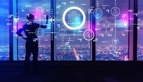 Slim stadsconcept met de mens door grote vensters bij nacht stock afbeelding