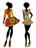 Slim stylish girls in short ornate colourful dresses. Slim stylized young models in short ornate colourful dresses, vector stencils isolated on the white Stock Photos