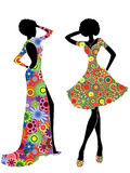 Slim stylish women in ornate ethnic dresses. Slim stylized young models in ornate colourful motley ethnic dresses, vector stencils isolated on the white Royalty Free Stock Photo