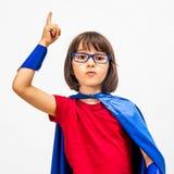 Slim super heldenkind die haar vinger voor verrassend idee opheffen Stock Foto's