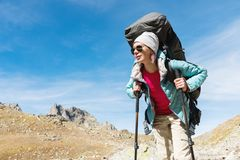 A hiker girl in sunglasses with a backpack and tracking sticks rises to a high rock against the background of rocks and. Slim and sympathetic Girl hiker in stock images
