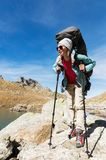 A hiker girl in sunglasses with a backpack and tracking sticks rises to a high rock against the background of rocks and royalty free stock images