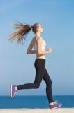 Slim tall girl running along the beach Royalty Free Stock Photo