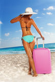 Slim tall woman with luggage on white sand beach Royalty Free Stock Images