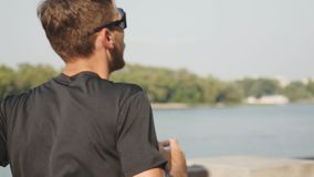 Free Slim Tanned Caucasian Man Running Near River. Young Athletic Man In Black T-shirt And Sport Glasses Runs At City In Morning. Close Stock Photos - 158230373