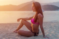 Slim tanned model in bikini posing on beach sitting sand in the light of morning at sunrise with mountains and sea in stock image