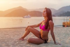 Slim tanned model in bikini posing on beach sitting sand in the light of morning at sunrise with mountains and sea in stock photography