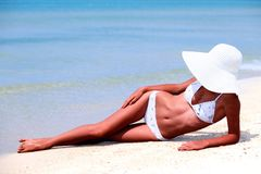 Slim tanned woman on a beach. Royalty Free Stock Image