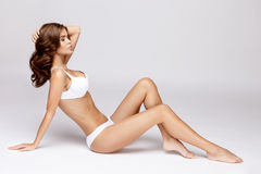 Slim tanned woman's body over gray background Stock Image