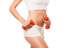 Slim tanned woman's body with red dumbbells on a Royalty Free Stock Images